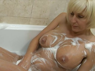 Playful blonde milf with big bosom plays around