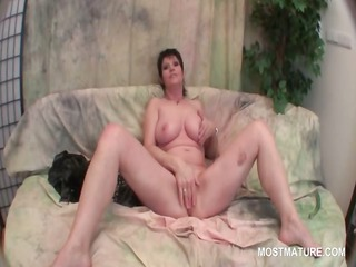 Busty mature brunette stuffing her cunt with a
