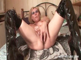 Mature in latex boots masturbating pussy with
